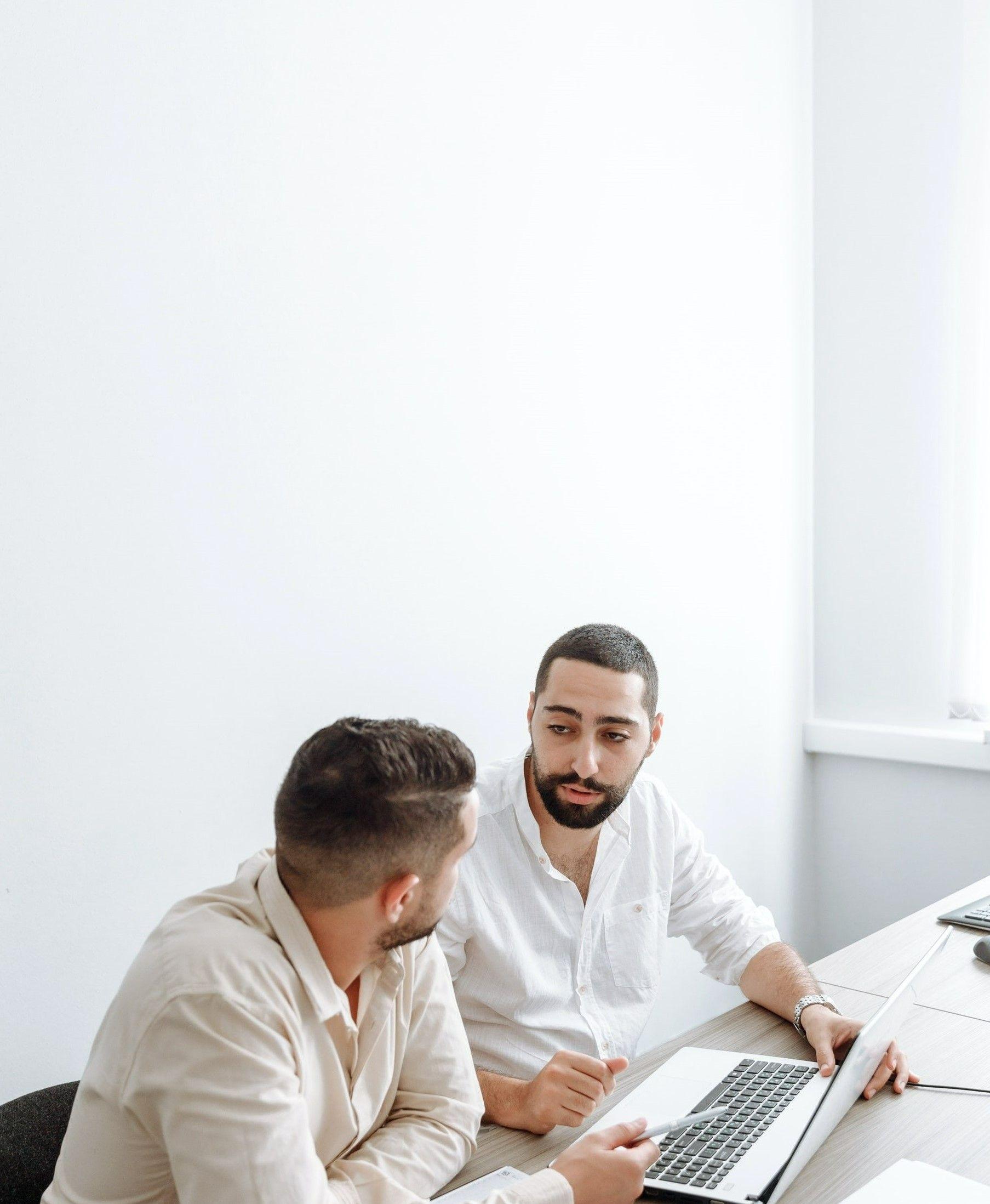 На фото два мужчины в офисе обсуждают план развития на ноутбуке