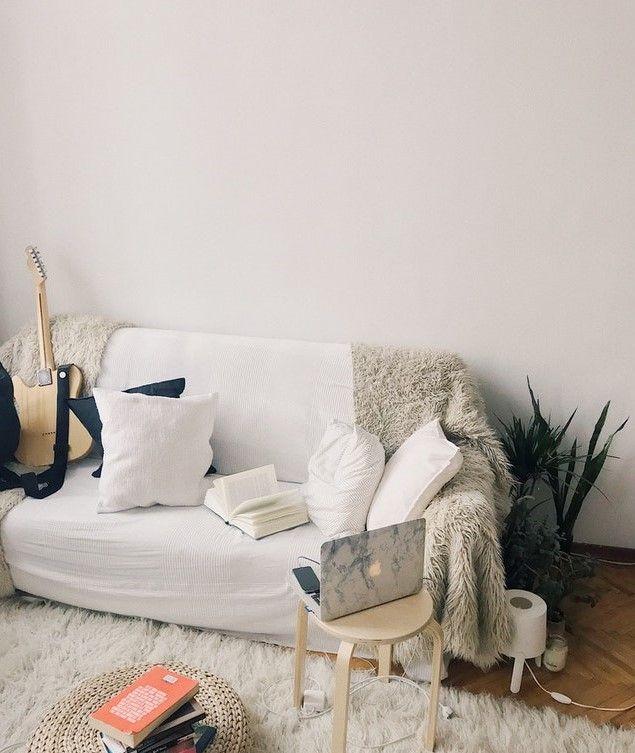 Фото комнаты с диваном на котором лежит гитара, книга, подушки и рядом стоит стол с ноутбуком