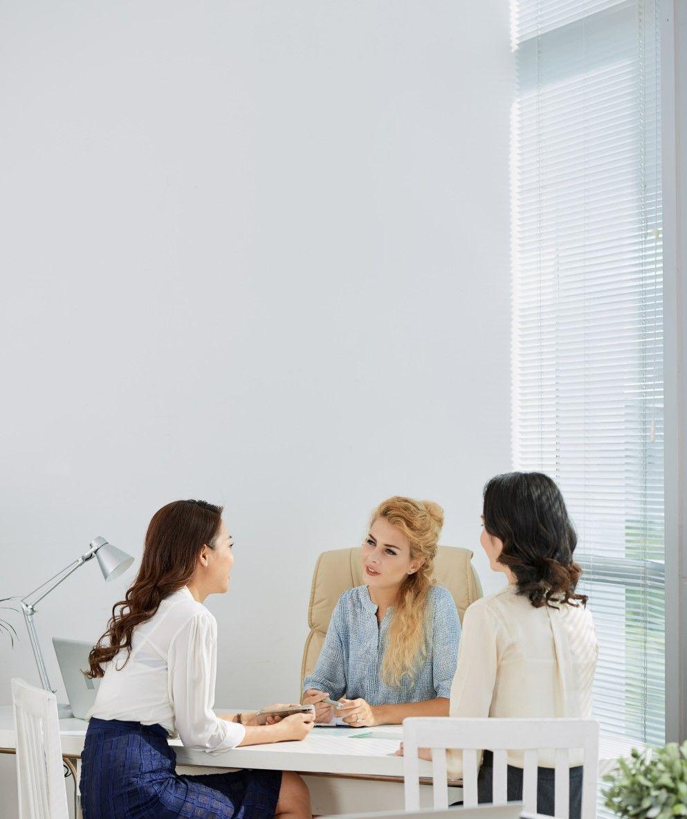 На фото изображён офис в котором за столом три девушки обсуждают развитие компании