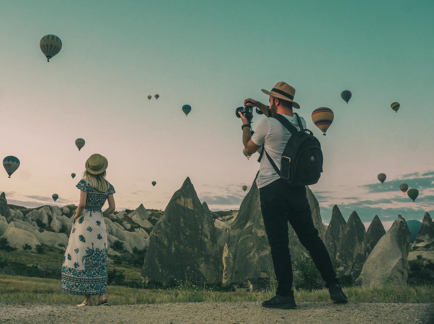 Фото на котором человек в закате фотографирует воздушный шар